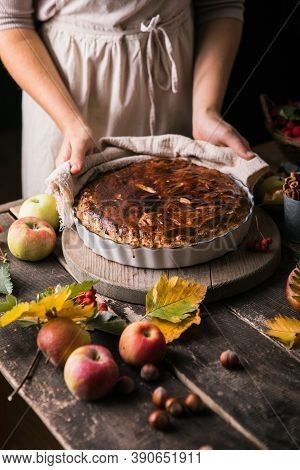 Homemade Apple Pie Surrounded By Fresh Fruits, Nuts, Apples In Woman Hands. Homemade Delicious Apple