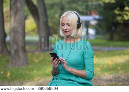 A Young Woman 25-30 Years Old In The Park Listening To Music With Headphones From Her Phone,selectiv