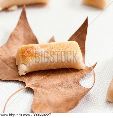 closeup of a hueso de santo, bone of the hole, a confection of Spain traditionally eaten on All Saints Day, placed on a dry leaf next to some other huesos de santo on an off-white textured surface