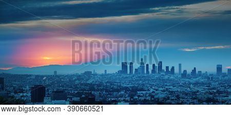 Los Angeles skyline at sunrise, panoramic city view from Hollywood Hills.