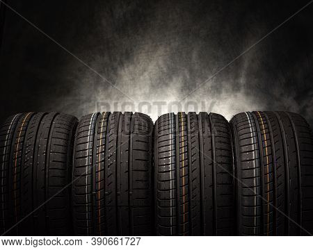 Tire Stack Background. Car Tires On A Black Background. Four Wheels.