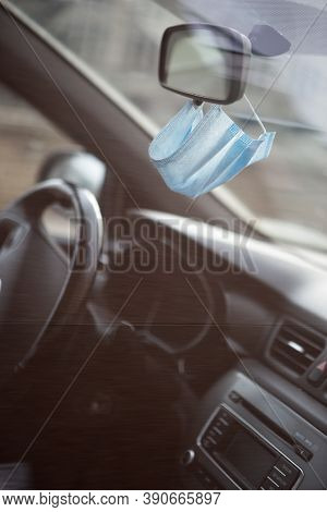 Medical Face Mask Hanging On Rear View Mirror Inside The Car. For Protect Himself From Bacteria And