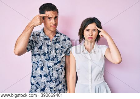 Beautiful couple wearing casual clothes pointing unhappy to pimple on forehead, ugly infection of blackhead. acne and skin problem
