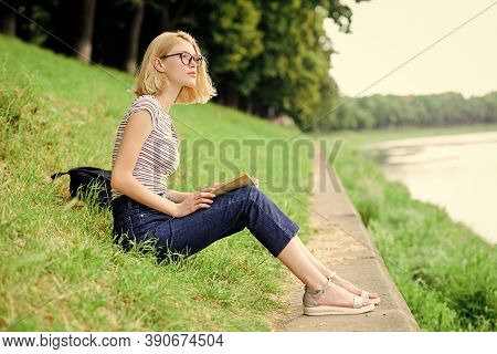 Girl Sit On Green Grass Near River. Vacation Season. Summer Vacation. Girl Relaxing At Riverside Aft
