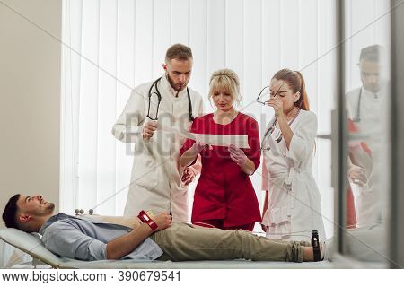 Training With Interns. A Young Blonde Doctor Gives A Lecture To Interns In The Office, Discussing Th