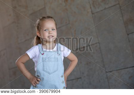 Cute Kid Girl 3-4 Year Old Wearing Trendy Clothes Posing In Cityoutdoors. Looking At Camera. Childho