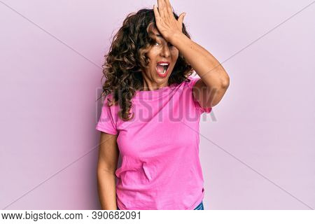 Middle age hispanic woman wearing casual clothes surprised with hand on head for mistake, remember error. forgot, bad memory concept.