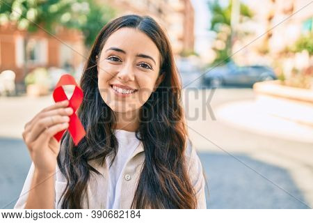 Young hispanic woman smiling happy holding red hiv ribbon walking at the city.