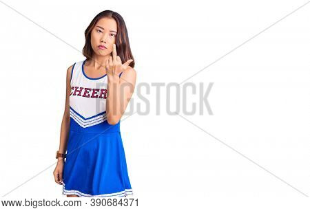 Young beautiful chinese girl wearing cheerleader uniform showing middle finger, impolite and rude fuck off expression