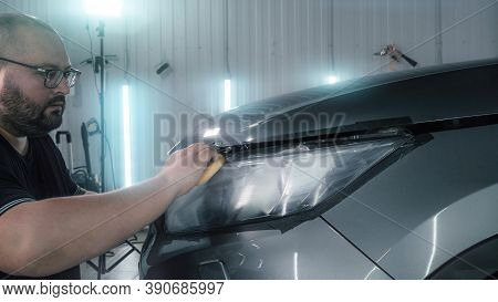 Car Detailing. Polisher Applies Special Polishing Compound Or Paste Or Wax To Optics Of Car Headligh