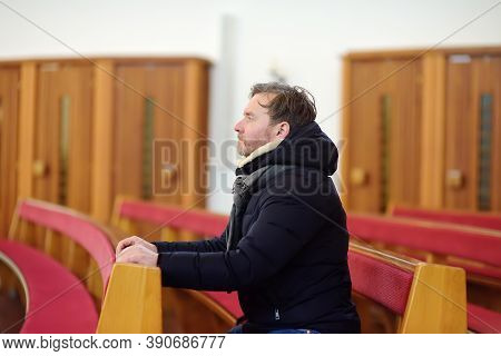 Religious Middle Age Man Praying And Meditating In Catholic Church. Person Begging For Forgiveness A