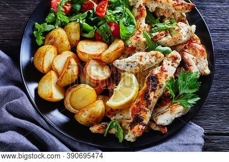 Mediterranean Meal: Grilled Chicken Strips With Baked Potato Halves, Lemon And Fresh Salad Of Arugul