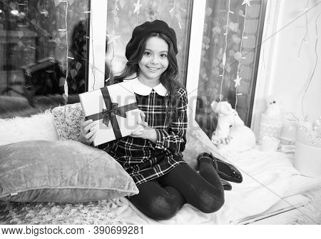Kid At Home Relaxing On Cozy Window Sill. Magic Moment. Happy Winter Holidays. Small Girl Opening Gi