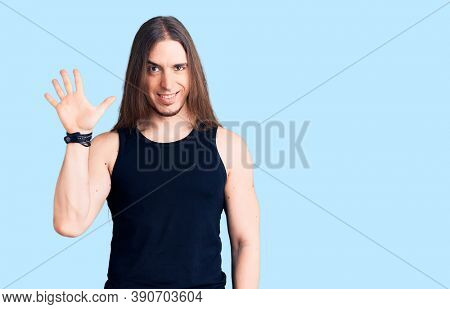Young adult man with long hair wearing goth style with black clothes showing and pointing up with fingers number five while smiling confident and happy.