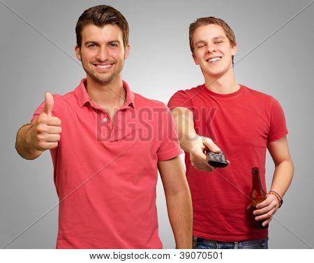 Happy Young Man Gesturing In front Of Man Enjoying Television On Grey Background