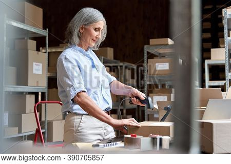 Older Mature Female Online Store Small Business Owner Worker Packing Package Scanning Postal Shippin
