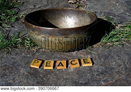 Singing Bowl On A Stone Outdoors And Letters Peace. Translation Of Mantras. Transform Your Impure Bo