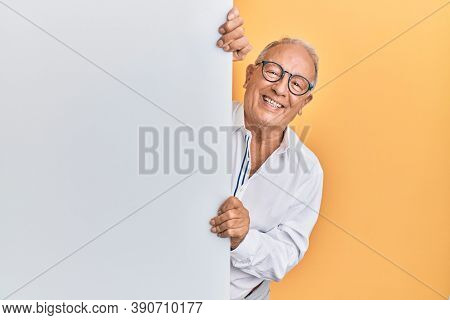 Senior caucasian man holding blank empty banner looking positive and happy standing and smiling with a confident smile showing teeth