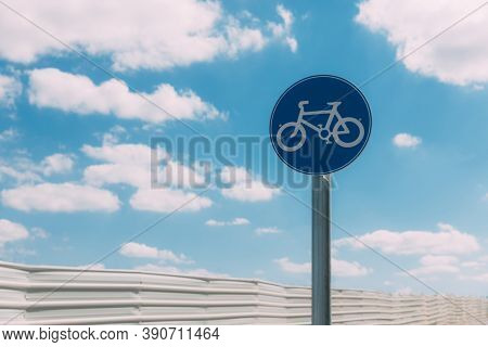 Close-up View Of Round Blue And White Bicycle Lane Sign Against A Fence And Blue Sky With Clouds. Ou
