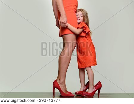 Little Girl Grow Up. Daughter Wearing Mothers High Heel Shoes. Mother Love. Learning To Be A Woman.