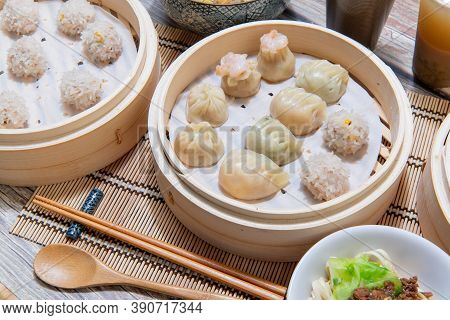 Steamed Xiaolongbao And Steamed Dumplings Served In A Traditional Steaming Basket (.close Up)