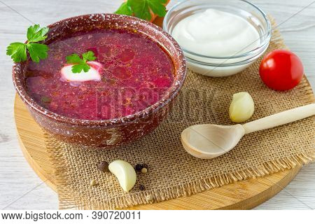 In A Clay Bowl, Hearty Vegetable Soup Borscht With Sour Cream On The Kitchen Board.