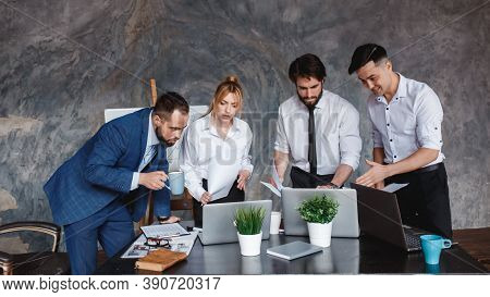 The Business Team Looks At The Laptop Screen. The Concept Of Waiting For The Result Of A Business Tr