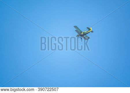 Retro Green Biplane Plane In The Blue Sky. Old Airplane Against Blue Sky