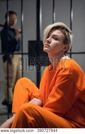 A Beautiful Young Girl Is Placed Under Arrest In An Asian Prison. Sitting In A Cell. In The Backgrou