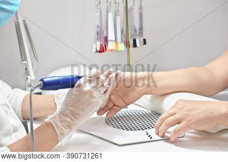 Beauty Salon, Manicure, Nail Polish Procedure. Professional Hardware Manicure Using Electric Machine