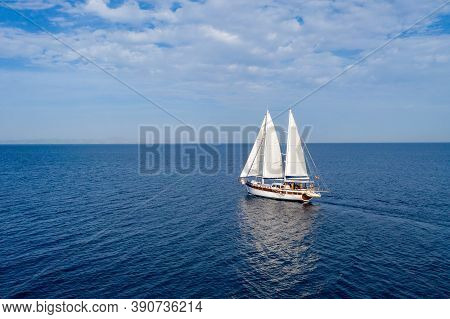 Sailing Boat With White Sails In The Open Sea, Cloudy Blue Sky
