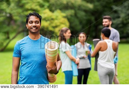 fitness, sport and healthy lifestyle concept - happy smiling indian young man with mat over group of people meeting for yoga class at summer park