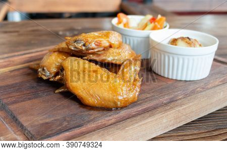 Barbecue Chicken Wings On Wooden Plate With Side Dishes