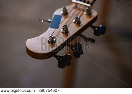 Tuning Pegs And Fretboard Bass Guitar Close Up On The Background Of The Musicians Apartment With Cop