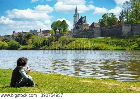 A Woman Sitting In The Grass Near A River