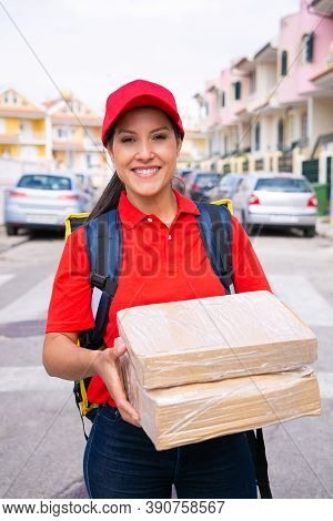 Portrait Of Happy Deliverywoman Holding Carton Boxes And Carrying Thermal Backpack. Young Brunette L