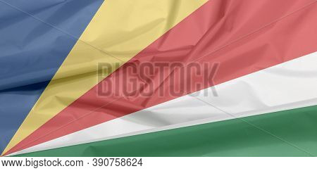 Fabric Flag Of Seychelles. Crease Of Seychelles Flag Background, Five Oblique Bands Of Blue Yellow R