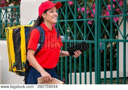 Confident Latin Courier Walking, Delivering Order, Smiling And Working On Post. Young Deliverywoman
