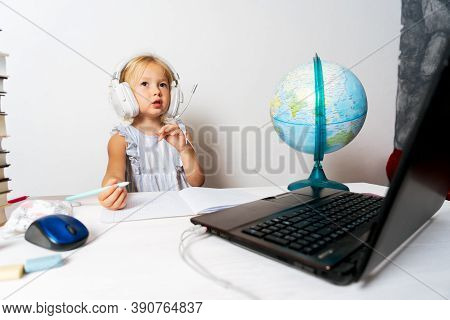 A Girl In Quarantine With A Laptop Is Undergoing School Training Remotely.