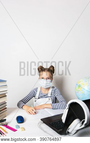A Girl In Quarantine Wearing A Mask With A Laptop Is Undergoing School Training Remotely.