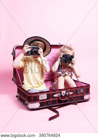 Travel: Children A Little Boy And Girl Play In Tourists, Sit In A Big Red Suitcase And Take Pictures