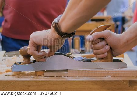 Professional Man Carpenter Using Spokeshave Or Plane To Shape And Smooth Wood Board On Workbench At