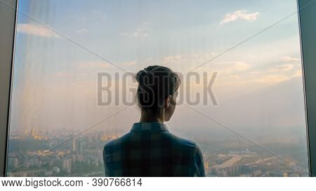 Back View Of Woman Silhouette Looking At Cityscape Through Window Of Skyscraper. Summer Time, Cloudy