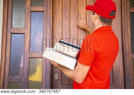 Confident Male Courier Delivering Order And Knocking On Door. Caucasian Deliveryman Wearing Red Cap