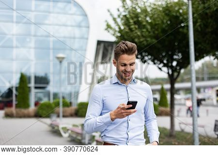 Handsome Office Worker Holding Smartphone And Smiling. Happy Young Man Using Mobile Phone Apps, Text