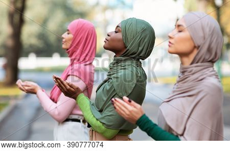 Three Islamic Ladies Praying Standing Together Outside Wearing Traditional Hijab Headscarf And Moder