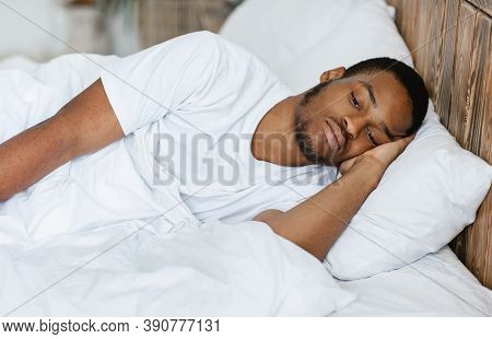 Male Depression And Apathy. Depressed Black Guy Lying Awake Thinking Of Problems Having Insomnia In