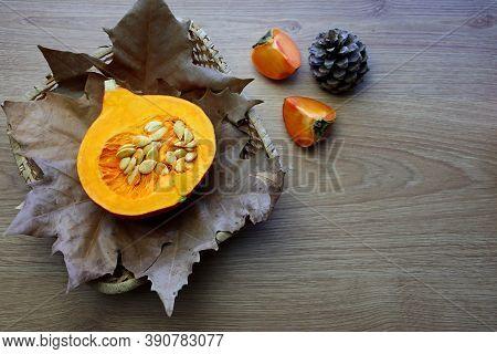 A Cutaway Hokkaido Pumpkin Lies On Autumn Leaves In A Wicker Basket. Autumn Still Life With Pumpkins