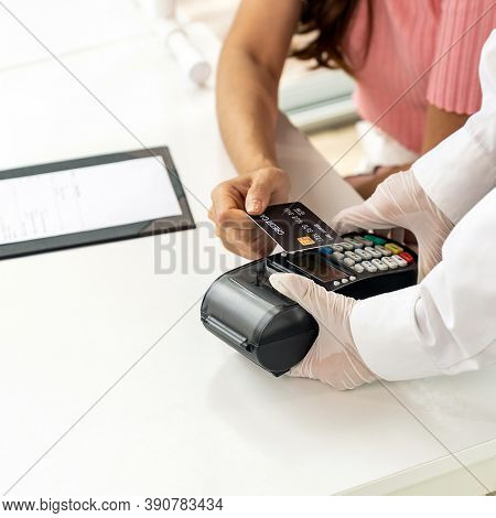 Close up Asian woman customer make contactless credit card payment after eating out in new normal social distance restaurant to reduce touching. Online contactless and technology concept.