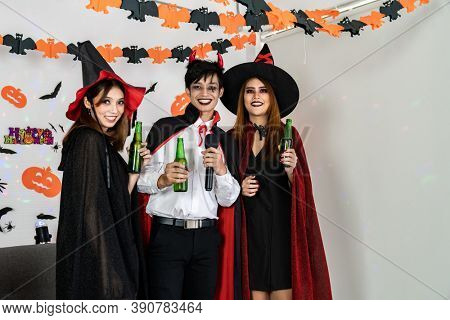 Portrait group of friends asian young adult people celebrate Halloween party carnival festive. They wear Halloween costume sing a song and cheers. Halloween celebrate and international holiday concept